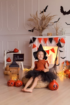 Ragazza in costume da strega di halloween con zucche