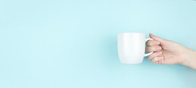 Tazza di caffè del mattino della stretta della mano della ragazza. copia spazio. sfondo blu.