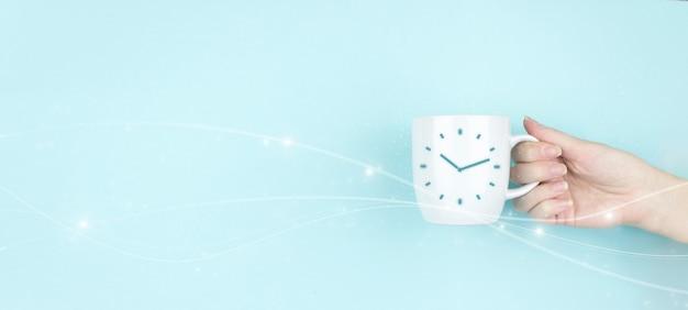 Tazza di caffè del mattino della tenuta della mano della ragazza con l'icona del segno dell'orologio su fondo blu. concetto grafico dell'intervallo di durata della gestione del tempo