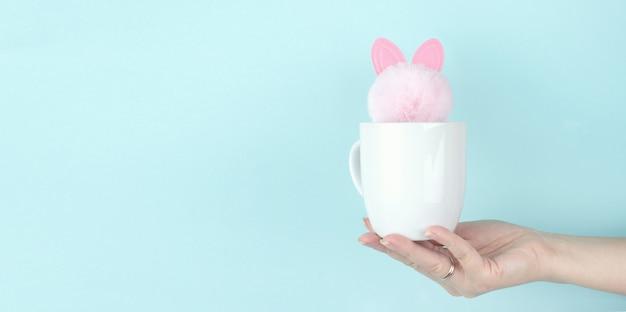 Ragazza mano tenere tazza di caffè del mattino con il giocattolo di coniglio rosa all'interno. copia spazio. sfondo blu.