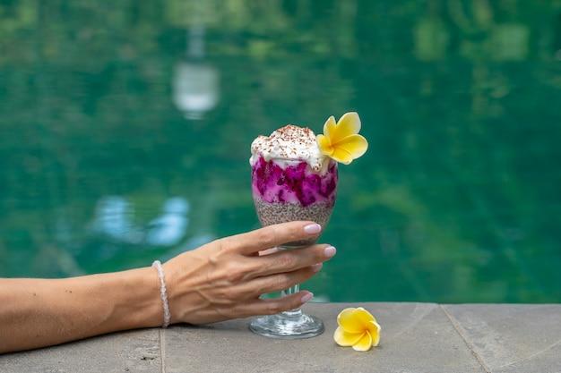 Mano della ragazza che tiene un bicchiere con budino di semi di hia sullo sfondo dell'acqua della piscina, primo piano. budino di semi di chia con frutta del drago rosso e yogurt bianco in un bicchiere per colazione