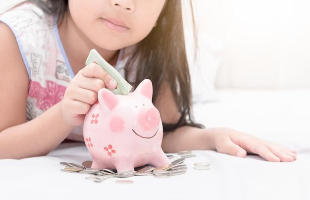 La mano della ragazza ha messo i soldi al porcellino salvadanaio sulla camera da letto