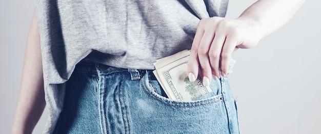 Mano della ragazza che mette i soldi nella tasca dei jeans