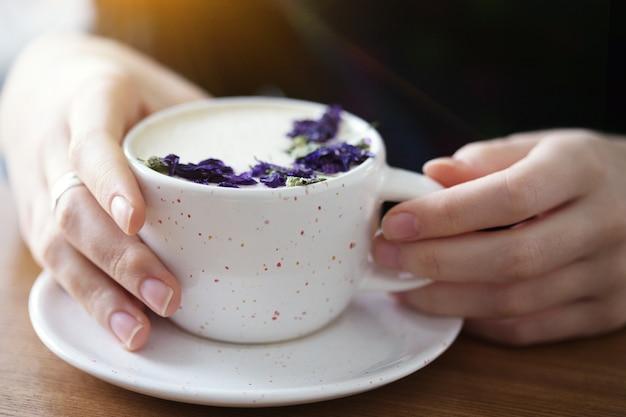 Mani della ragazza che tengono una tazza di cappuccino