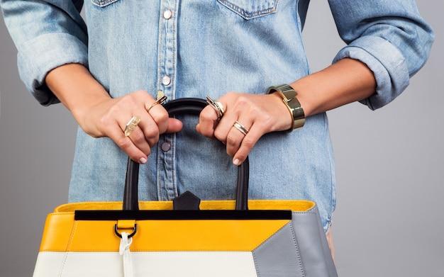 Mani della ragazza che indossano anelli che tengono la borsa gialla