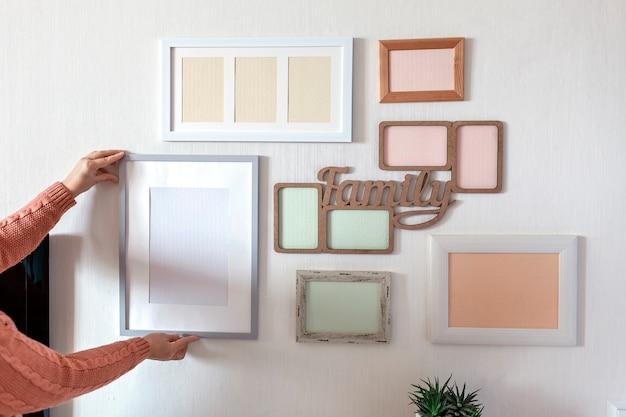 Ragazza che appende il telaio sul muro bianco con set di diverse cornici vuote verticali e orizzontali per creare una galleria di foto di famiglia, per catturare un momento, modello di mockup sul muro bianco, stile di vita