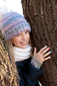 La ragazza sorridente felicemente con le braccia intorno all'albero con una bella manicure.