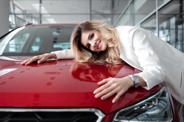 Ragazza felice di comprare la sua nuova macchina rossa.