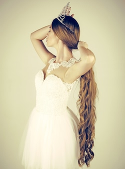 La ragazza ha un trucco alla moda e capelli sani su sfondo grigio
