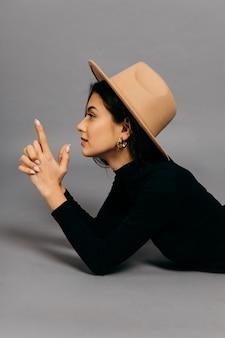Ragazza in un cappello astratto che mira una pistola dalle mani su uno sfondo grigio