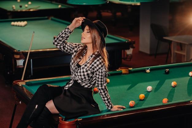 Una ragazza con un cappello in un club di biliardo si siede su un tavolo da biliardo. giocare a biliardo.
