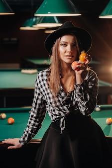 Una ragazza in un cappello in un club di biliardo con le palle in mano. giocare a biliardo.