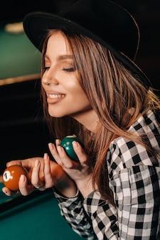 Una ragazza con un cappello in un club di biliardo con le palle in mano