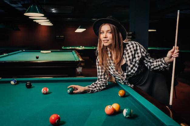 Una ragazza con un cappello in un club di biliardo con una stecca e le palle in mano. giocare a biliardo.