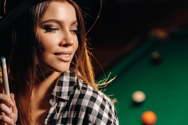 Una ragazza con un cappello in un club di biliardo con una stecca in mano. gioco di biliardo.