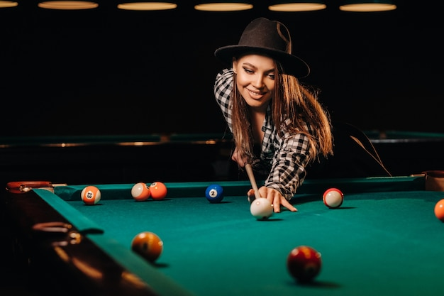 Una ragazza con un cappello in un club di biliardo con una stecca in mano colpisce una palla.