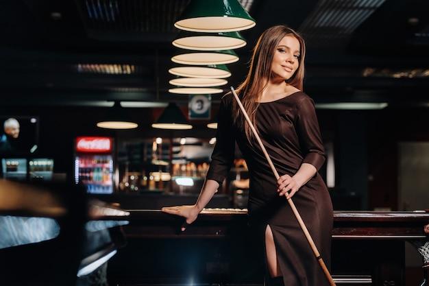 Una ragazza con un cappello in un club di biliardo con una stecca in mano
