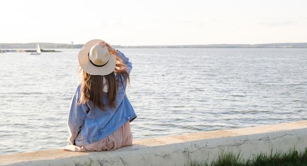 Ragazza in cappello e vestito blu che si siede su una spiaggia sabbiosa, picnic.
