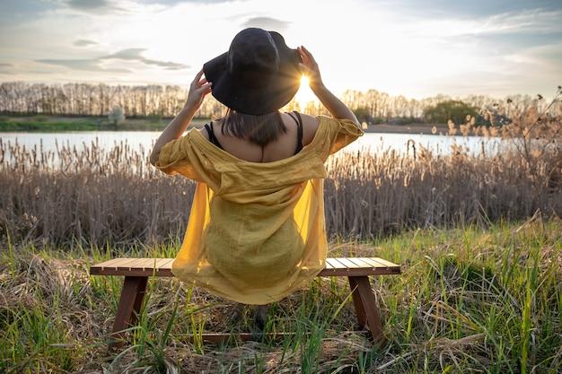 Una ragazza con un cappello e in stile casual si siede su una panchina vicino al lago al tramonto