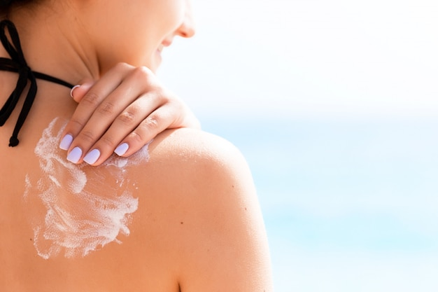 Ragazza con cappello sta applicando la protezione solare sulla schiena per proteggere la sua pelle