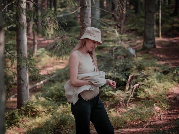 La ragazza con il cappello sta pensando mentre si trova nella foresta