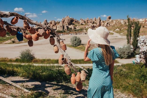 Una ragazza con un cappello e un vestito rosa sta vicino a un albero appeso con piatti di ceramica in capadocia