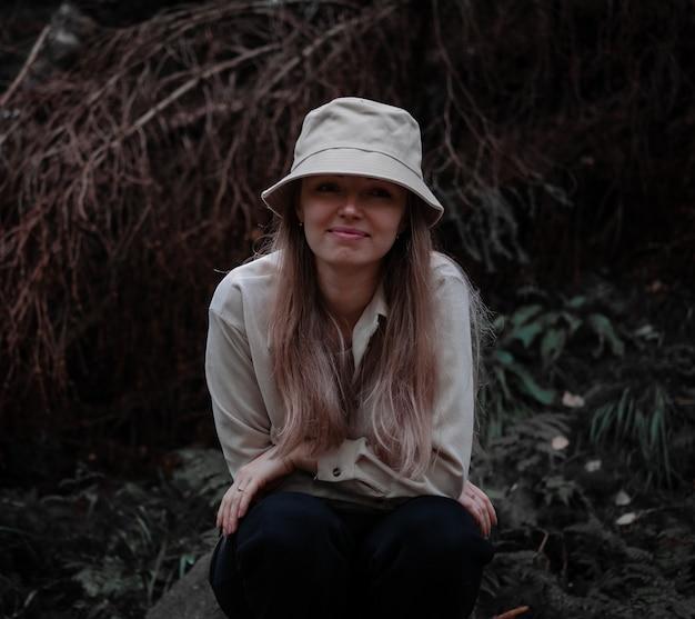 La ragazza con un cappello si siede e sorride nella foresta