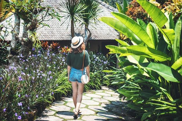 Una ragazza con un cappello cammina in una giornata di sole attraverso il territorio di un hotel di lusso a ubud. una giovane donna cammina lungo un sentiero circondato da fiori luminosi e piante tropicali, vista da dietro, bali, ubud.
