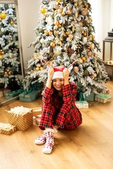 Ragazza divertendosi e celebrando il natale. sullo sfondo albero di natale decorato con regali.
