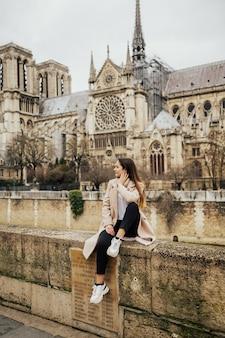 Ragazza divertirsi vicino alla cattedrale di notre-dame a parigi, francia.