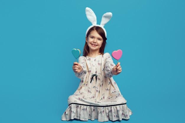 Ragazza con due biscotti a forma di cuore su bastoncini con orecchie da coniglio pasquale