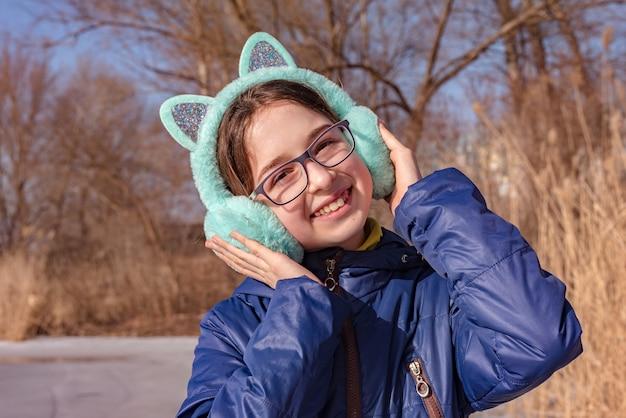 Ragazza in cuffia. ragazza con occhiali e paraorecchie. ragazza dell'adolescente che gode della giornata di sole primaverile
