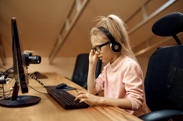 La ragazza con le cuffie lavora su pc, piccola blogger