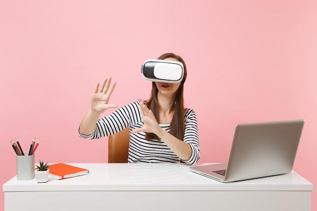 La ragazza con l'auricolare della realtà virtuale sulla testa tocca qualcosa come premere il pulsante o indicando lo schermo virtuale mobile lavora alla scrivania con il laptop