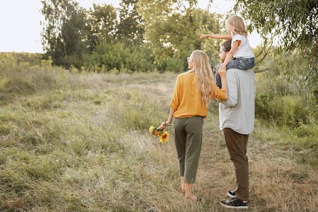 La ragazza al collo di suo padre indica a sinistra durante una passeggiata. spazio libero per il testo