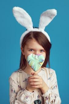 Ragazza che si nasconde dietro un biscotto a forma di cuore e indossa orecchie da coniglio sopra il blu