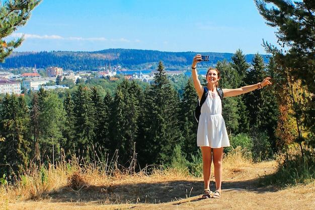 Una ragazza durante un'escursione si fa un selfie con il telefono o si connette in montagna. una donna con uno smartphone. parco centrale a sortavala. viaggio in russia. repubblica di carelia.