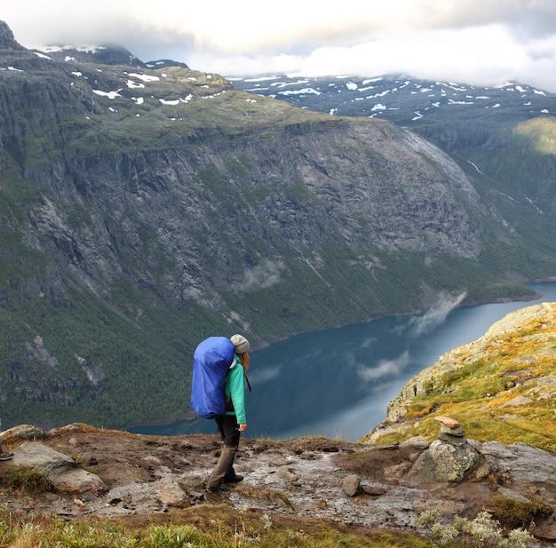 Escursionista ragazza che va per sentiero presso le montagne norvegesi