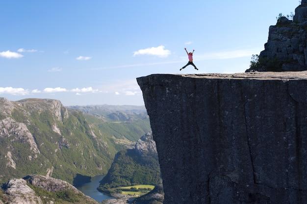Escursionista ragazza saltando su preikestolen, preikestolen -famosa scogliera alle montagne norvegesi