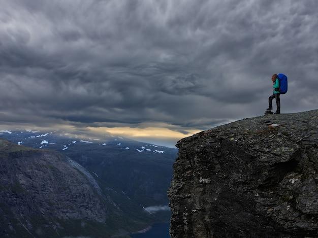 Escursionista ragazza in piedi sulla scogliera e guardando le montagne, preikestolen -famosa scogliera alle montagne norvegesi