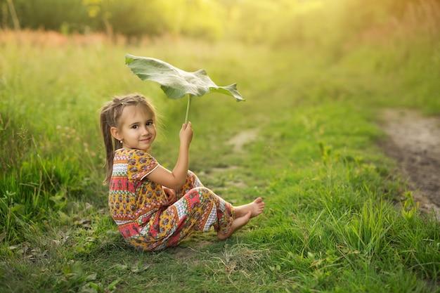 La ragazza tiene la grande foglia di bardana come l'ombrello.