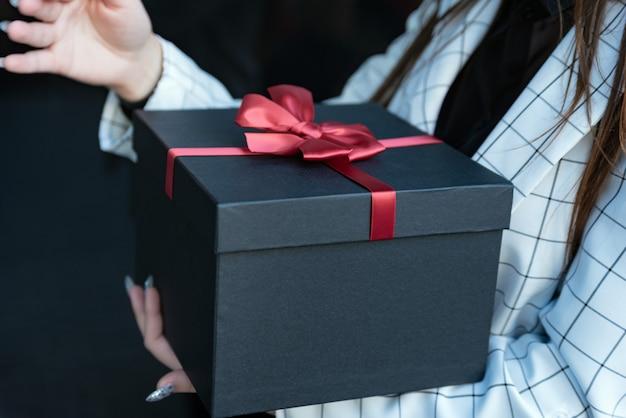 Ragazza con una bella confezione regalo nelle sue mani. scatola nera con fiocco rosso in mani femminili su sfondo nero. copia spazio