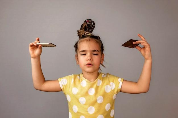 Ragazza che tiene barrette di cioccolato bianco e nero in entrambe le mani e meditando come yogi