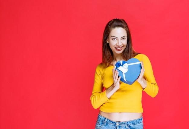 Ragazza con una confezione regalo a forma di cuore blu