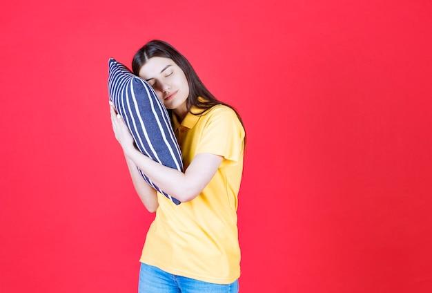 Ragazza che tiene un cuscino blu con strisce bianche e dorme.