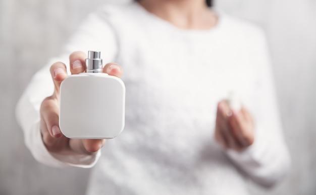 Bottiglia della holding della ragazza di profumo.