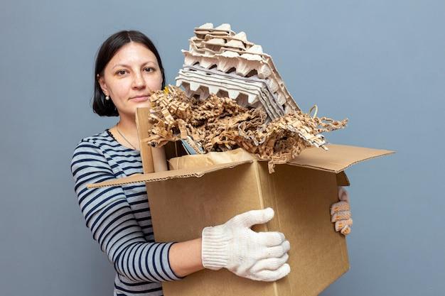 Scatola di cartone della tenuta della ragazza con il fumetto, carta straccia usata, immondizia per riciclare