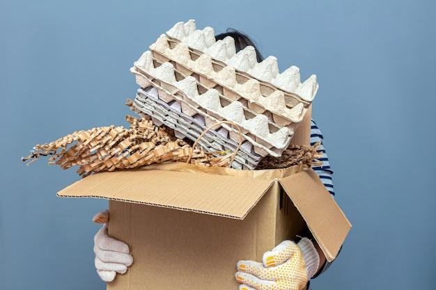 Scatola di cartone della tenuta della ragazza con carta, fumetto usato rifiuti, immondizia per riciclare