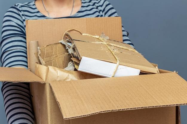 Ragazza con scatola di cartone con carta, cartone animato usato rifiuti, immondizia per il riciclaggio