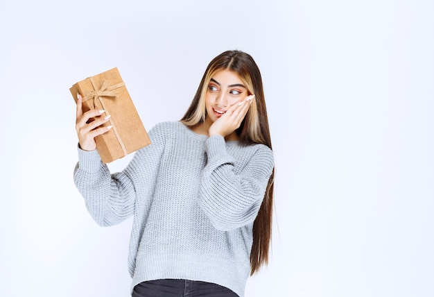 Ragazza in possesso di una confezione regalo di cartone e sembra sorpresa.